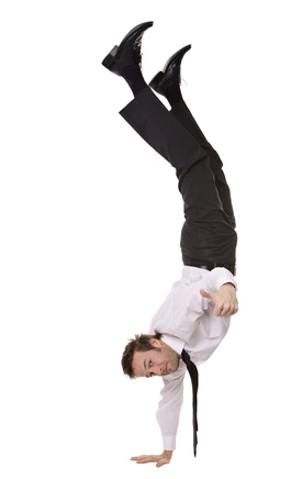 Businessman doing handstand and giving a thumbs up
